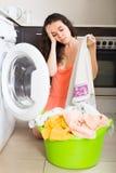 Tired woman near washing machine Royalty Free Stock Image