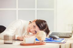 Tired woman at office desk in the evening. Tired woman at the office desk in the evening Royalty Free Stock Photos