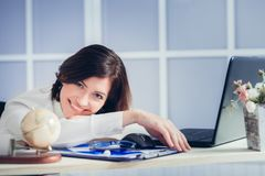 Tired woman at office desk in the evening Stock Photos