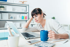 Tired woman at office desk. Tired sleepy woman working at office desk and holding a cup of coffee, overwork and sleep deprivation concept Stock Images