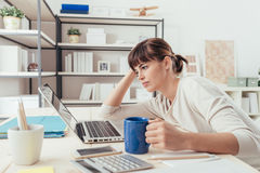 Tired woman at office desk. Tired sleepy woman working at office desk and holding a cup of coffee, overwork and sleep deprivation concept Royalty Free Stock Images