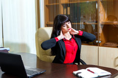 Tired woman in office holding hands on the aching neck Royalty Free Stock Images