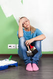 Tired woman  with paint tools Stock Photo
