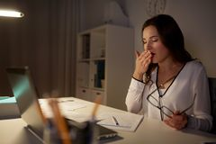 Tired woman with papers yawning at night office. Business, overwork, deadline and people concept - tired woman with papers and laptop yawning at night office Stock Image