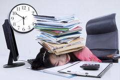 Tired woman with a pile of document Royalty Free Stock Photography