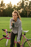 Tired woman quenches thirst after riding a bike Royalty Free Stock Photo