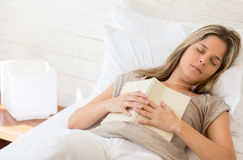 Tired woman reading a book Stock Image
