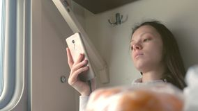 Tired woman is reading a book in smartphone travelling on a long distance train. Tired woman is reading a book in smartphone travelling on a long distance train stock video