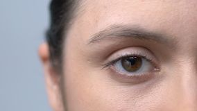 Tired woman with red blood vessels in eyes slowly blinking looking into camera. Stock footage stock footage
