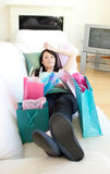 Tired woman relaxing after shopping. Tired woman relaxing on her sofa after shopping Royalty Free Stock Image