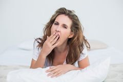 Tired woman resting in bed. And yawning Royalty Free Stock Images