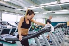 Tired woman resting over treadmill after training Royalty Free Stock Photos