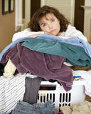 Tired woman resting on pile of laundry. Unhappy, sad, tired woman resting on large, messy pile of laundry Royalty Free Stock Photo