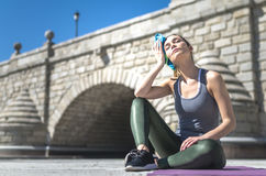 Tired woman resting, relaxing and drinking water with towel after workout and do yoga stock photos