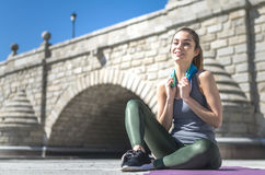 Tired woman resting, relaxing and drinking water with towel after workout and do yoga.  Royalty Free Stock Images
