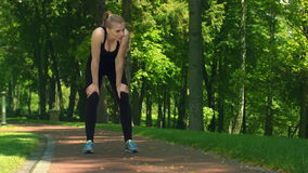 Tired woman resting after running hard at park. Fit girl relax after jogging stock footage