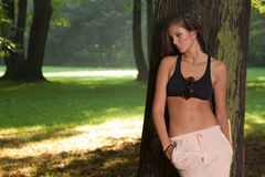 Tired woman resting in the wood. Young attractive girl wearing sport outfit is resting before jogging Royalty Free Stock Photography