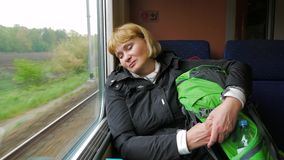The tired woman rides train b is sleeping against the window. Tired blonde woman with his travel backpack going after the high-speed train travel and sleeping stock video