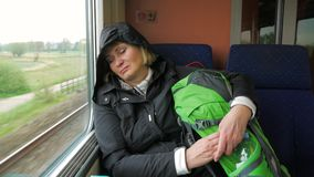 Tired woman rides on the train and sleeps against the window. Tired blonde woman asleep in a high-speed train,which travels from the journey. Sleeping in a stock video