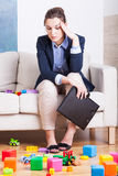 Tired woman in room full of kids toys Royalty Free Stock Photography