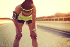 Tired woman runner taking a rest after running hard Stock Image