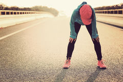 Tired woman runner taking a rest after running hard. On city road Stock Photo