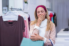 Tired woman with shopping bags yawning Royalty Free Stock Image