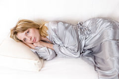 A tired woman in a silver silk. A tired blond woman in a silver silk robe Royalty Free Stock Images