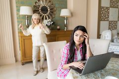 Senior mother and her daughter working with laptop. Tired Woman Sits At The Laptop And Looks Sideway While Her Blurred Senior M Other Dances On The Background stock photo