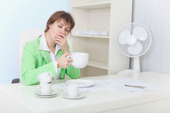 Tired woman sits at table with big cup of coffee Royalty Free Stock Images