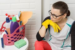 Tired woman sitting on bathroom floor with cleaning supplies and equipment royalty free stock image