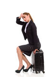 Tired woman is sitting at the black suitcase Royalty Free Stock Images