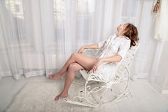 Tired woman sitting on a chair in front of the window. Photo of a tired woman in a shirt sitting on a vintage chair in front of the window Royalty Free Stock Images