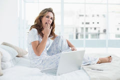 Tired woman sitting on cosy bed with laptop Stock Photos