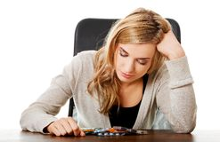 Tired woman sitting at the desk with lot of pills Stock Photo