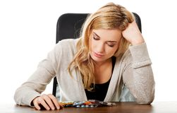 Tired woman sitting at the desk with lot of pills Royalty Free Stock Image