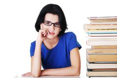 Tired woman sitting at a desk with stack of books Stock Image