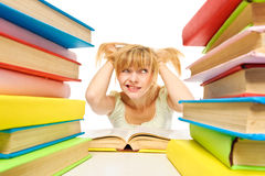 Tired woman sitting at the desk surrounded with piles of books. Isolated Royalty Free Stock Image
