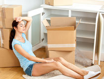 Tired woman sitting on the floor after unpacking Stock Photography