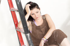 Tired woman sitting at the foot of a stepladder Stock Image