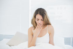 Tired woman sitting on her bed yawning. With eyes closed Royalty Free Stock Image