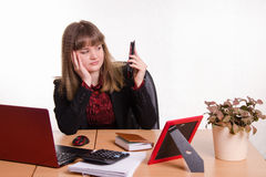 Tired woman sitting office desk, looking at phone Stock Images
