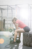 Tired woman sitting on tire in crossfit gym Royalty Free Stock Photo