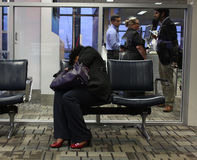 Tired woman sleeping in airport Stock Photo