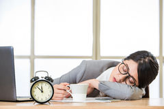 Tired woman are sleeping and holding coffee. Tired woman are sleeping at desk in the office Stock Photography