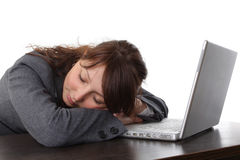 Tired woman sleeping with laptop. Tired woman sleeping in front of the computer isolated on white Royalty Free Stock Photo