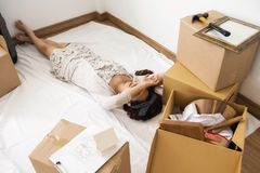 TIred woman sleeping  at new home. Tired Asian wife woman sleeping on white fabric sheet of empty new home room after moving many boxes and luggage and cleansing Royalty Free Stock Photos