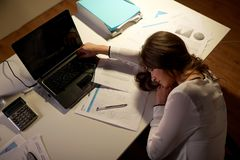 Tired woman sleeping on office table at night. Business, overwork, deadline and people concept - tired woman with laptop and papers sleeping on table at night Stock Photo