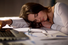 Tired woman sleeping on office table at night Stock Images