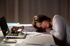 Tired woman sleeping on office table at night. Business, overwork, deadline and people concept - tired woman with laptop and papers sleeping on table at night Royalty Free Stock Photos